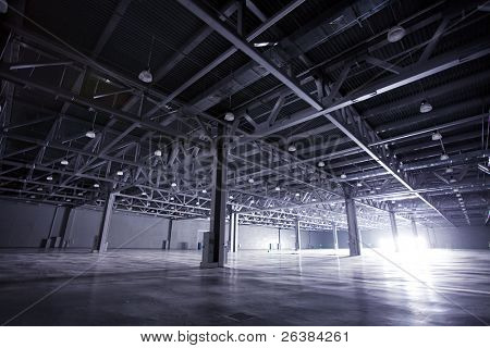 Modern empty dark storehouse with light at the end