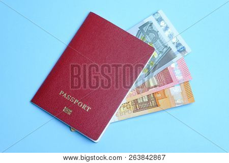 Euro Banknotes Invested In A Foreign Passport Isolated On A Blue Background. Travel To Europe.