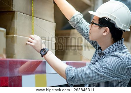 Male worker hand using tape measure for measuring dimension of product in cardboard box. Shopping lifestyle in warehouse concept poster