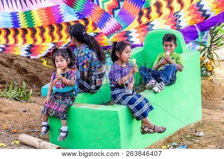 Santiago Sacatepequez, Guatemala - November 1, 2017: Indigenous Maya Children Eat Ice Cream With Mot
