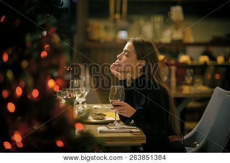 Woman Enjoy Wine In Restaurant. Girl With Long Hair Celebrate New Year And Christmas. Festive Fashio