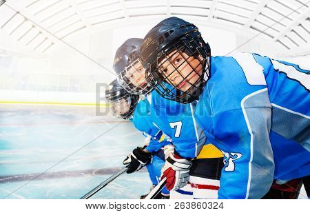Young Hockey Players Standing In Line On Ice Rink