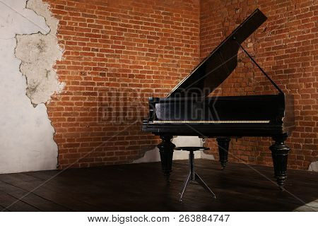 Grand Piano With Raised Lid And Stool Near Brick Wall