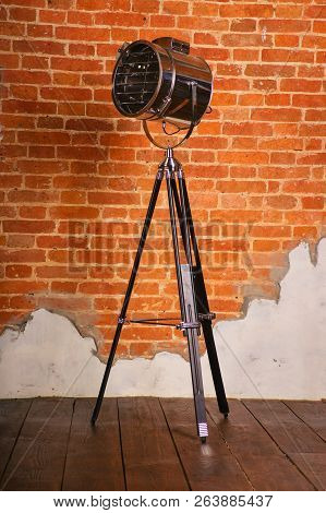 Old Fashioned Floor Lamp On Tripod Near The Brick Wall.