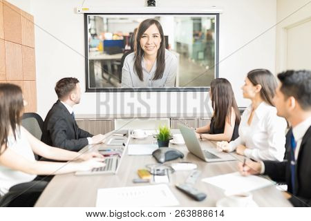 Multiethnic Male And Female Coworkers Attending Presentation In Boardroom