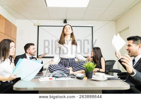 Young Businesswoman Meditating In Lotus Position While Colleagues Yelling During Negotiation In Offi