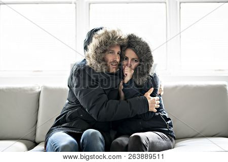 Couple Have Cold On The Sofa At Home With Winter Coat