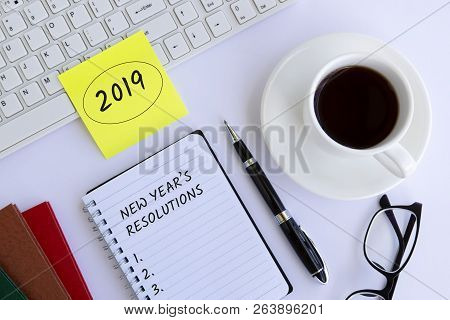 2019 New Year's Resolution Text On Notepad On Top Of White Office Desk