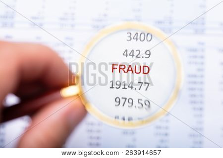 Man Examining Fraud Word On Financial Report