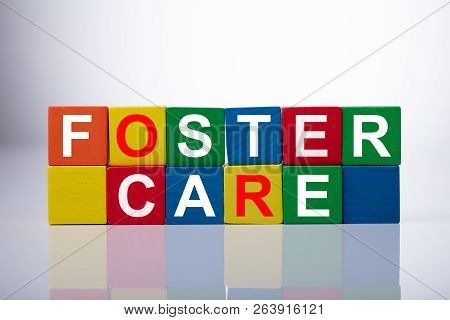 Close-up Of Foster Care Cubic Blocks On Reflective Background