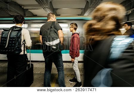 Paris, France - Oct 13, 2018: Blur Train Passing Fast As Commuters Large Crowd Of People Waiting In