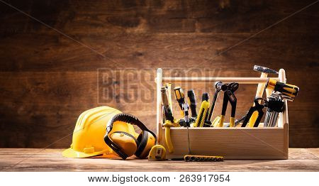 Safety Equipment Near Toolbox With Various Worktools On Wooden Surface
