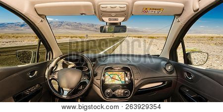 Looking Through A Car Windshield With View Over A Hot Desert Road In Death Valley National Park, Cal
