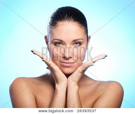 Beautiful woman with water drops on face against blue background
