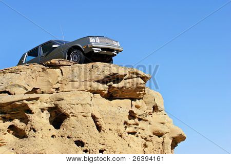 car dangerously close to the edge of a sandstone cliff
