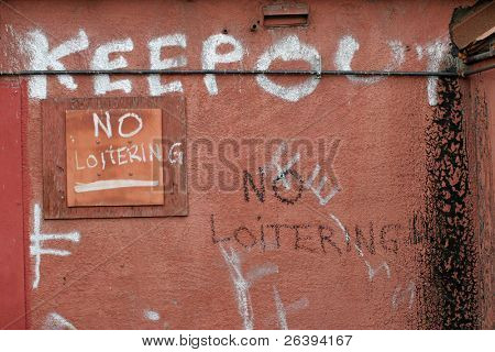 keep out and no loitering, strong message painted on a back wall along an alley