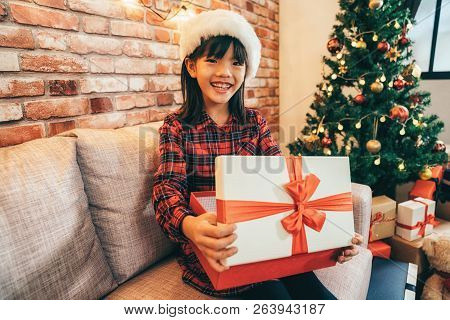 Girl Holding Christmas Box Sitting Next To Tree