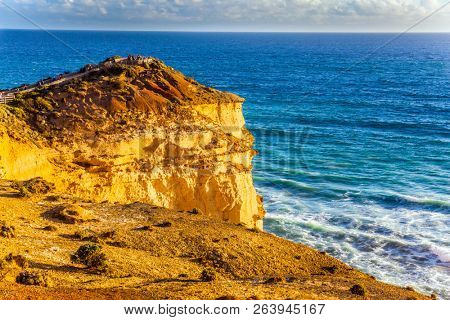 The Great Ocean Road. Steep and rocky ocean shore of Australia. Powerful ocean surf at sunset. The concept of exotic, active and photo-tourism