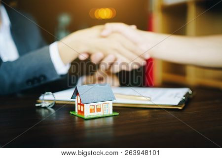 Real Estate Agents Agree And Customer Shaking Hands After Signing Contract Documents For Realty Purc
