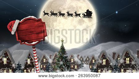 Digital composite of Santa in sleigh with reindeer flying and Christmas sign in Winter wonderland