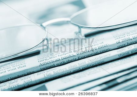 Eyeglasses Lie On A Pile Of Newspapers.blue Toned