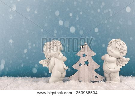 Two Christmas Cherub Baby Angels Statuettes On Snow With Wooden Tree Light Blue Background