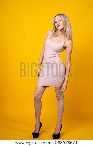 Sexy Blonde Girl Is Posing On Yellow Background Wearing Pink Short Dress.