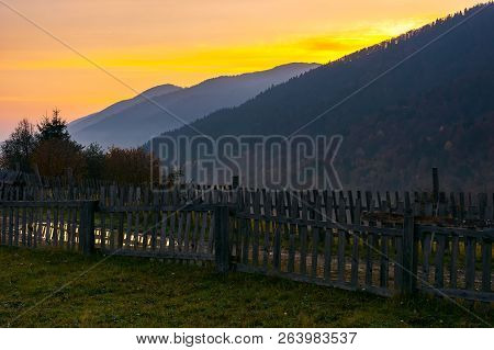 Village Outskirts In Mountains At Dawn. Wooden Fence Along The Road With Puddle. Deep Autumn Weather