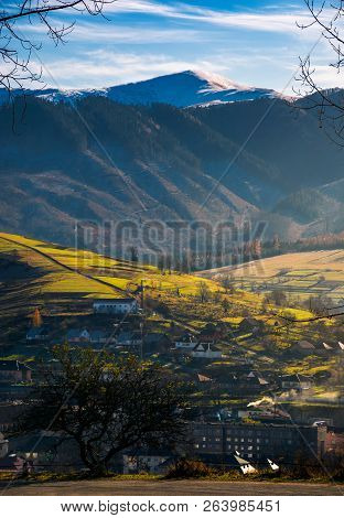 Lovely Countryside Scenery In Afternoon. Village Down In The Valley. Distant Mountain With Snowy Top