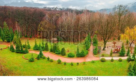Park With Playground In Autumn. Gloomy Rainy Weather In Mountains. Green Lawn And Leafless Forest In
