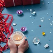 christmas spirit and holidays festivity. hands holding light candle. assortment of sparkle embellishments on blue background. poster
