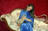 Pretty Teen Girl With Long Hair In A Blue Robe And Her Pet Cat Sitting On A Beautiful Sofa poster