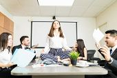 Young businesswoman meditating in lotus position while colleagues yelling during negotiation in office poster