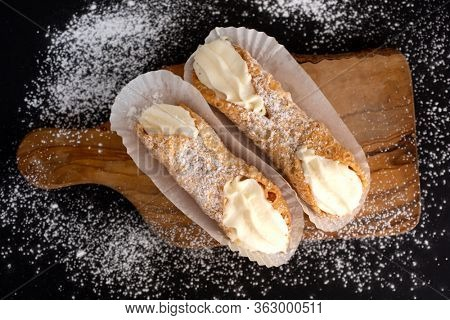 Top view of two fresh cannoli in paper on a cupboard on a black background powdered with sugar