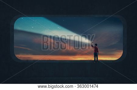 Young Man Light Up The Sky With A Flashlight During Dramatic Sunset .