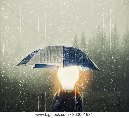 Man With A Lightbulb Instead Of Head Holding Umbrella While Raining .  Positive Mindset Concept.