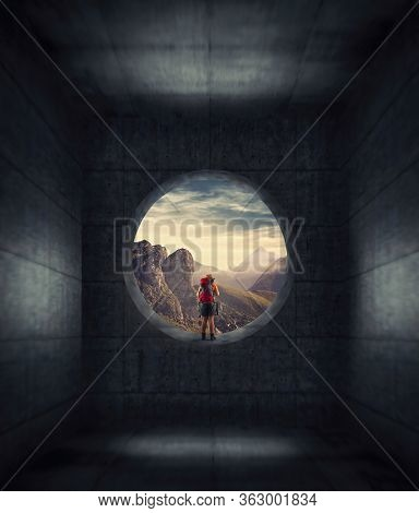 Traveler Looking Through Round Concrete Window To Mountain Landscape . Isolated In Dark Concrete Roo