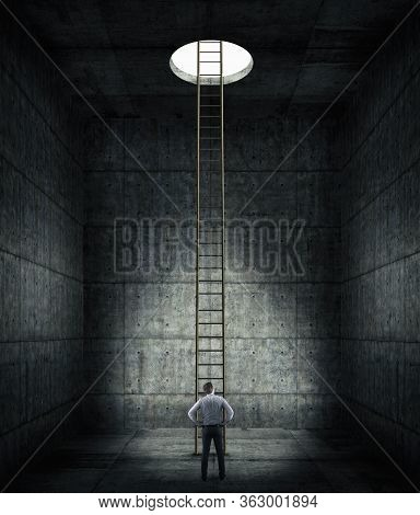 Businessman In A Dark Concrete Room With A Ladder To The  Hole . Finding Solution In Tough Times . W