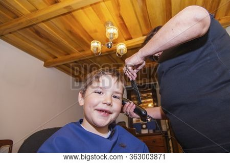 Grandmother Cutting Hair To His Little Grandson In Her Home Sewing Room. Living At Home During Lockd