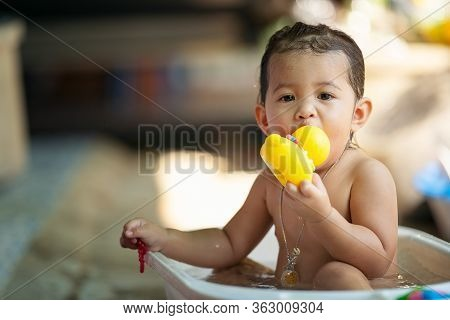 Bath Time Is Fun. Selective Focus Image Of A Cute Little Girl Taking A Bath And Playing With Rubber