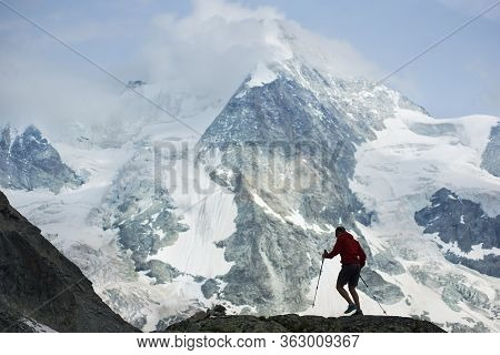 Male Hiker Climbing With Hiking Poles. Amazing, Rocky Mountain In Snow In The Pennine Alps On Backgr