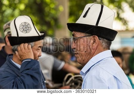 Osh, Kyrgyzstan - June 30, 2019: Two Men With Ak-kalpak Hat On The Livestock Market In Osh, Kyrgyzst