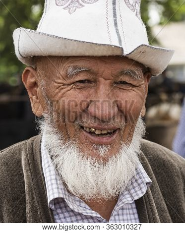 Osh, Kyrgyzstan - June 30, 2019: Man With Ak-kalpak Hat On The Livestock Market In Osh, Kyrgyzstan.