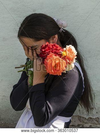 Rushon, Tajikistan - June 17, 2020: Shy School Girl In School Costume In Front Of The School At The