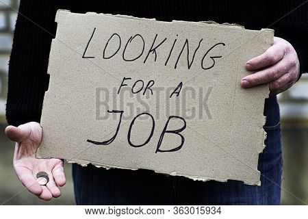The Unemployed Person Holds In His Hand The Cardboard Tablet With The Inscription Looking For A Job