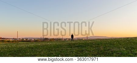 Caucasian Man From Back Looking To Industrial Part Of City Ceske Budejovice On Meadow At Sunset. Cze