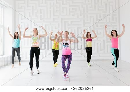 Group Of Young Women In Sportswear At Zumba Dance Fitness Class In White Fitness Studio