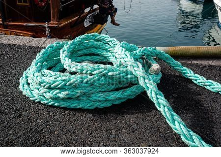Mooring Cable On The Pier. Close Up Of Nautical Moored Ropes, Blue Sea. Copy Space.
