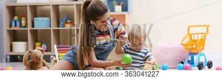 Teen Nanny And Cute Little Baby Playing With Toys At Home. Banner Design