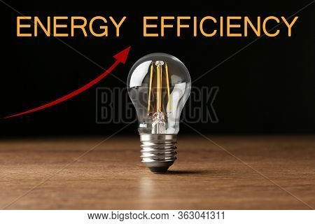 Energy Efficiency Concept. Vintage Filament Lamp Bulb On Wooden Table